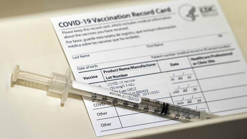 FILE - In this Wednesday, Dec. 16, 2020, file photo, a syringe containing a dose of the Pfizer...