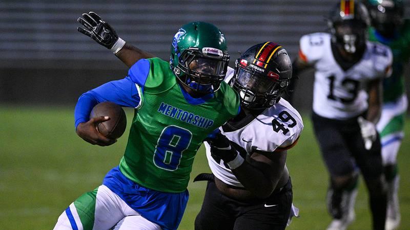 Mentorship quarterback Amauri Moye (8) gets tackled from behind by Brusly defensive lineman...