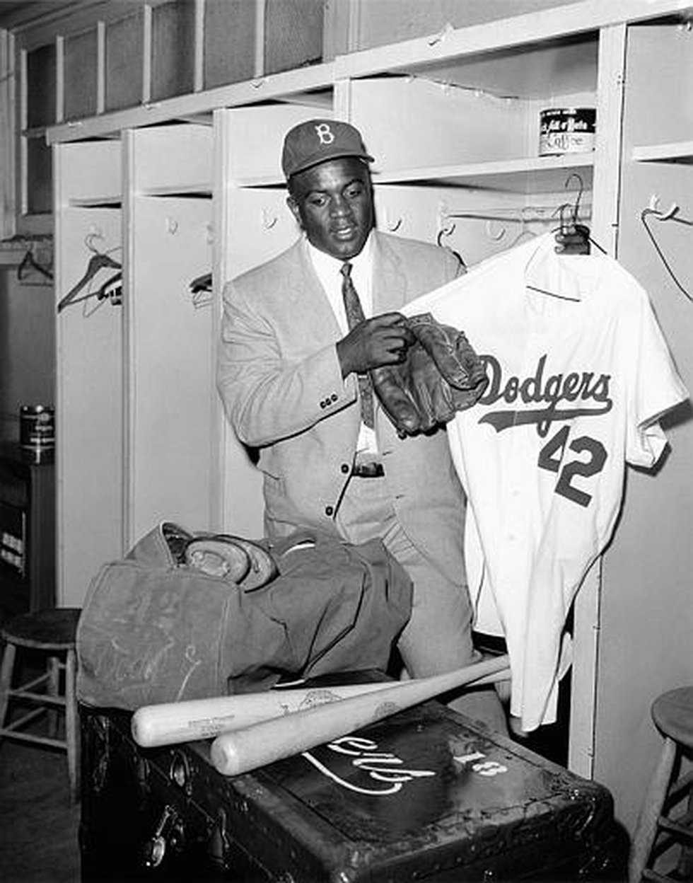Jackie Robinson, 38, empties his locker at the clubhouse of the Brooklyn Dodgers baseball club...