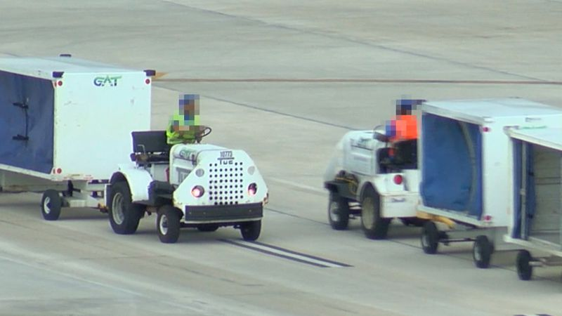 Two luggage transport vehicles for GAT Airline Ground Support are seen passing each other at...