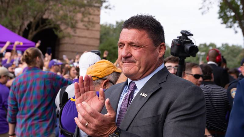 LSU head coach Ed Orgeron claps as he strolls through a sea of fans before a home game for the...