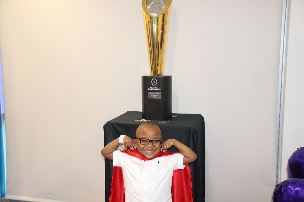 """""""Superman"""" poses with the national championship trophy"""