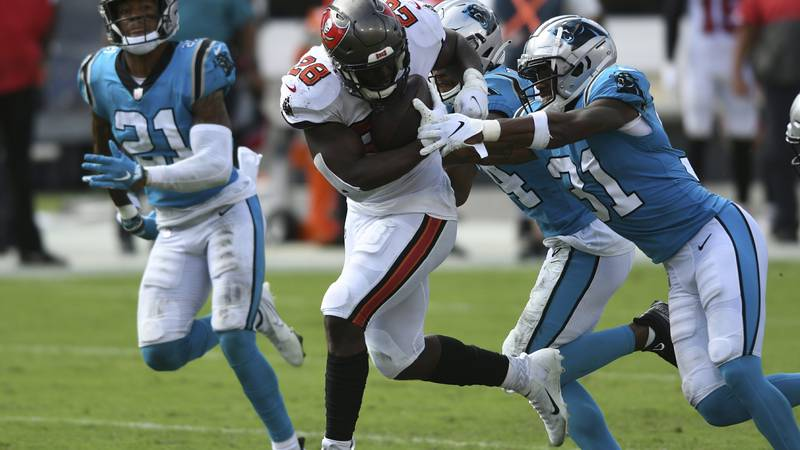 Tampa Bay Buccaneers running back Leonard Fournette (28) is stopped by Carolina Panthers strong...