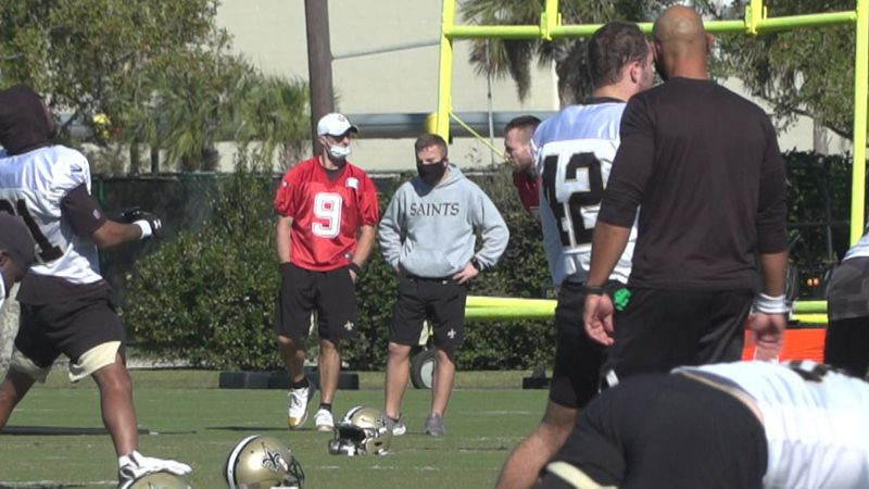 Saints quarterback Drew Brees watches on as his teammates stretch at practice