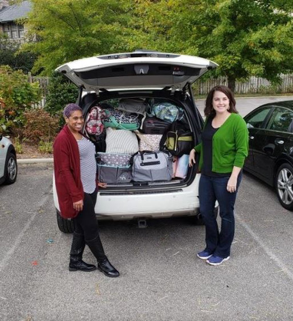 Chauntel Norris (L) and Maureen McDermott Williams (R) accepting donations of diaper bags and...