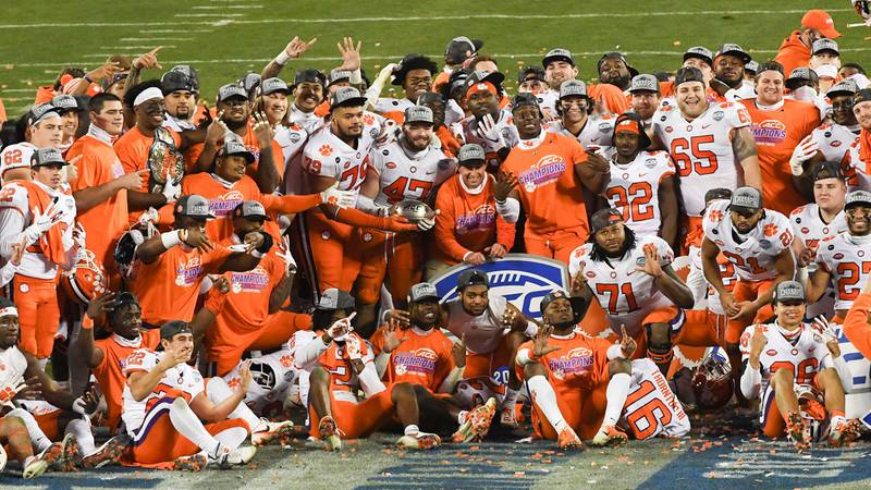 Clemson players and coaches pose after beating Notre Dame 34-10 in the ACC Championship game...