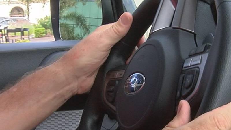 A senior citizen's hands on the steering wheel.