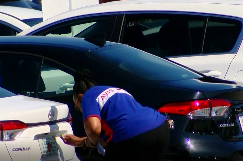 An Avis employee replaces the tags on a rental car at Myrtle Beach International Airport.