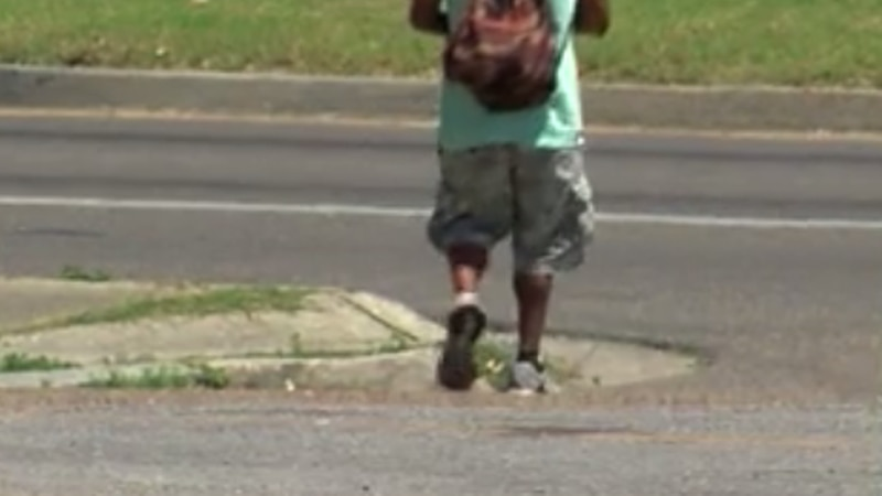 A person with a backpack walks in a working-class area.