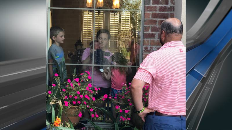 James Bamber waves to his family through the window of their home.