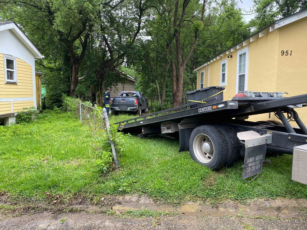 A tow truck operator prepares to tow a truck that was involved in a lengthy police chase in...