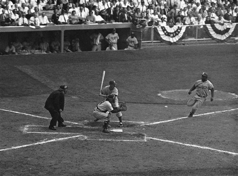 Brooklyn Dodgers third baseman Jackie Robinson (42) steals home and slides under catcher Yogi...