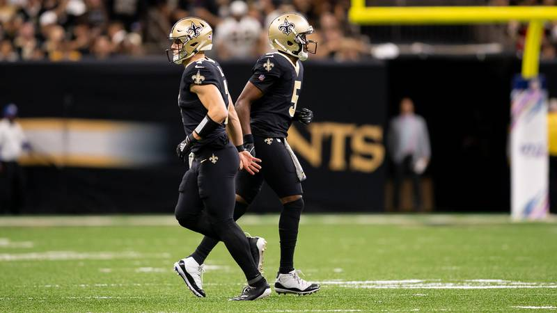 Saints quarterbacks Taysom Hill and Teddy Bridgewater overlap on the field during a 2019 game...