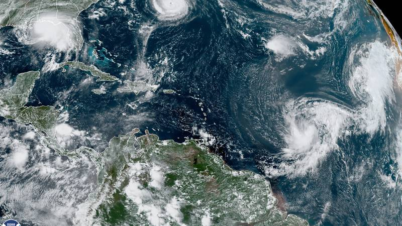 This satellite image provided by the NOAA shows five tropical cyclones churning in the Atlantic...