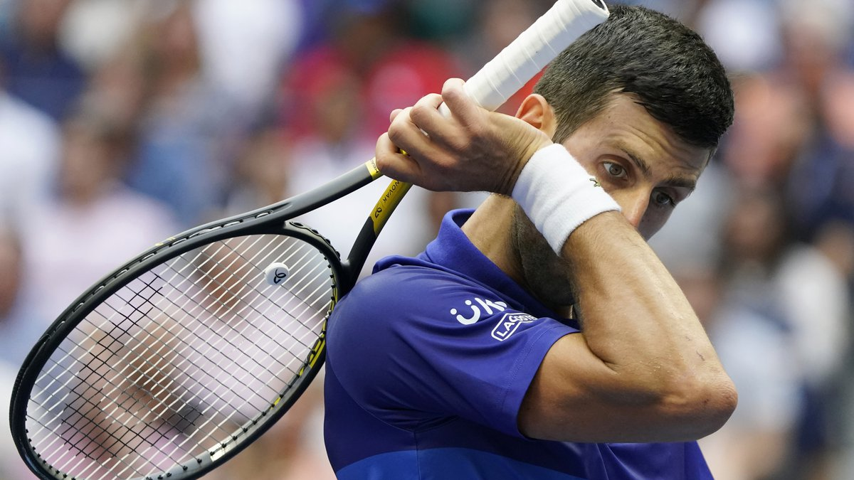 Novak Djokovic, of Serbia, wipes sweat from his face between points during the men's singles...
